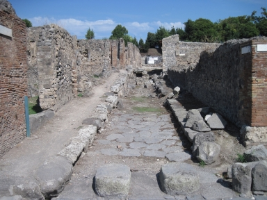 I.2 Pompeii, on left. September 2010. Looking east along Vicolo del Conciapelle, with the north (side) wall of  I.1.9, on right. Photo courtesy of Drew Baker.